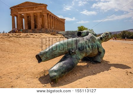 AGRIGENTO ITALY - AUGUST 12 2016: Bronze statue of the fallen Icarus by Igor Mitoraj installed in 2011 in front of the Ancient Greek (c.430 BC) Temple of Concordia in the Valley of the Temples.