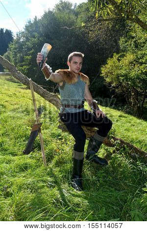 Young Medieval dressed one man, holds drinking horn high in the hand, looks forwards and sits on branch in the nature
