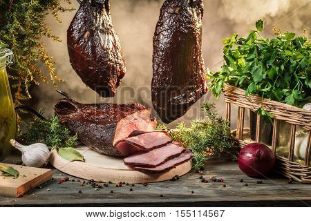 Freshly smoked ham in homemade smokehouse on old wooden table