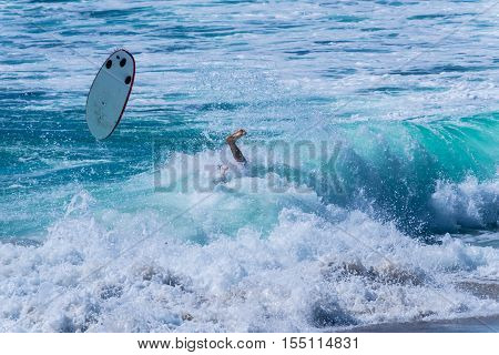 Surfer wiping out after a successful ride