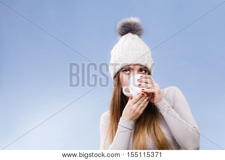 Woman in winter cap gray sports thermal underwear for skiing training holds mug with tea or coffee warming herself studio shot on blue.