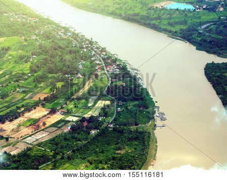 Arial view over small village near the river in Thailand. City skyline background.