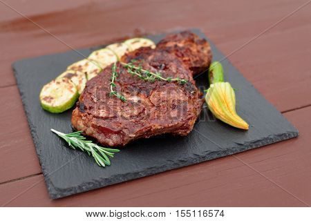 Rib eye steak with vegetables on a slate plate