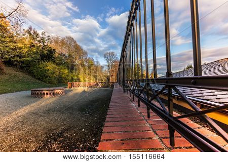 Ornamental iron fence path and trees illuminated by the setting sun. Moravian landscape Lysice.
