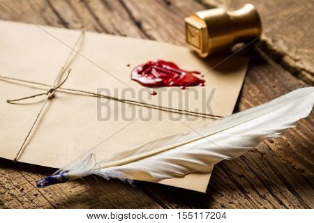 Closeup Of Feather On Envelope With Red Sealant And Metal Stamp