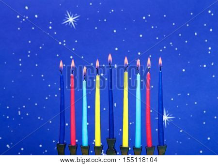 a nine-branched menorah (also called a Chanukiah or Hanukiah) burning candles to celebrate Hanukkah against a blue starry background.