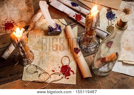 Antique Table Filled With Old Papers, Red Sealant And Candles