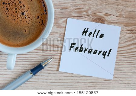 hello February on peace of paper near morning coffee cup at workplace background.