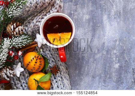 Traditional winter beverage mulled wine. Christmas drink. Gray background with knitted scarf