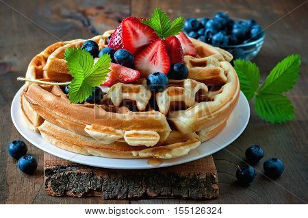 Belgian waffles with strawberries blueberries and syrup homemade healthy breakfast toned image selective focus
