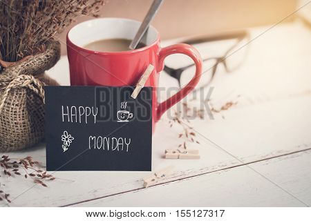 Happy Monday massage on notebook with cup of coffee and flower on wooden table