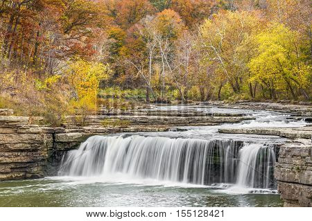 Lower Cataract Falls a wide waterfall in Owen County Indiana is surrounded by beautiful fall foliage.
