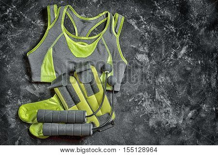 Sport fitness wear and equipment on the texture black background - gray with yellow lady's bra socks weights and skipping rope with unique beads instead of a rope. Copy space for your inscription.