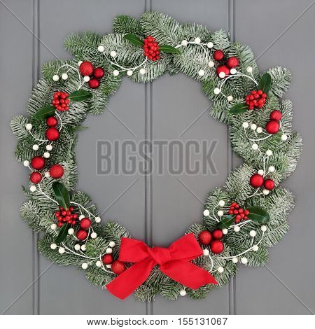 Christmas and advent wreath decoration with red baubles decorations, bow, holly and snow covered evergreen blue spruce fir over grey front door background.