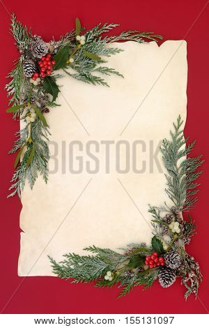 Winter and christmas abstract background border with holly, mistletoe, snow covered cedar cypress and pine cones on old parchment paper over red.