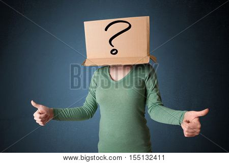 Young lady standing and gesturing with a cardboard box on her head with question mark