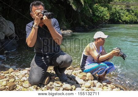 Kiulu,Sabah,Borneo-Oct 22,2011:Photographers taking photos near river bank using digital SLR camera at Kiulu river,Sabah,Borneo.Borneo is a nature photographer's dream among tourists.