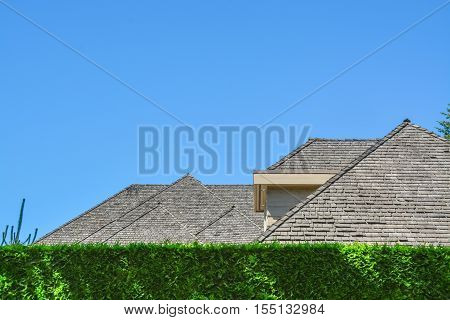 Residential house with massive roofs green hedge in front on blue sky background. Family house with big roofs tiled by wooden shingles