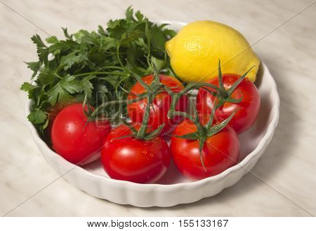 Tomatoes, lemon and parsley in a white round form with corrugated edges on a marble background. Summer allsorts of vegetables