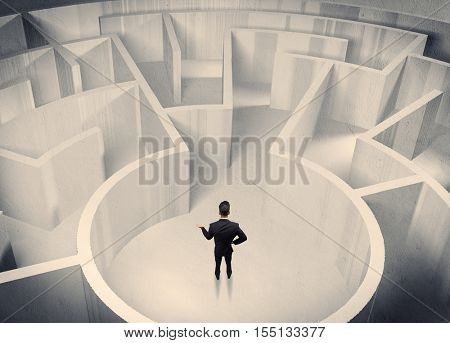 A confused businessman standing in the center of a maze surrounded with walls of the labyrinth