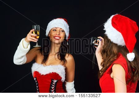 Two young girls in red dresses and Christmas hats Santa's photographed on a dark background