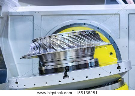 Metalworking. High-precision CNC machine processes steel turbine wheel.