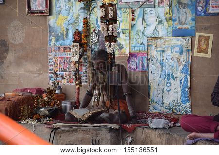 VARANASI, UTTAR PRADESH, INDIA - FEBRUARY 17, 2016 - Unidentified indian sadhu sitting and reading with images of indian gods on his back