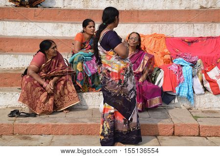 VARANASI, UTTAR PRADESH, INDIA - FEBRUARY 17, 2016 - Unidentified indian women with colorful dresses sitting and talking on the ghats