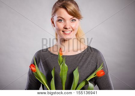 Celebration gift present flora nature beauty concept. Smiling female holding boquet. Young lady showing tulip flowers.
