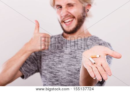 Successful guy showing broken cigarette making thumb up sign gesture. Winning with addicted nicotine problems stop smoking. Quitting from addiction concept.