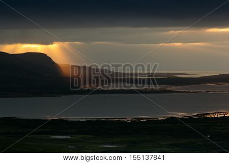 Storm sky with majestic golden rays of setting sun over sea. Arctic summer the tundra Norway.