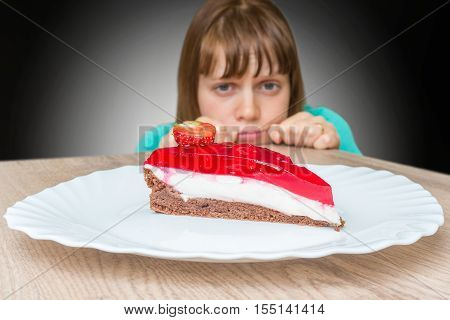 Young woman cannot resist the temptation and wants to eat sweet cake - dieting concept