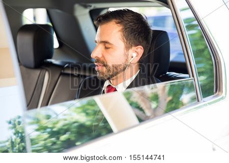 Businessman Relaxing With Music In A Car
