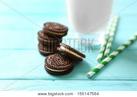 Tasty chocolate cookies and straws on wooden table