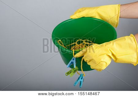 Human hands in rubber gloves hold washbowl with clotheslines and clothespins