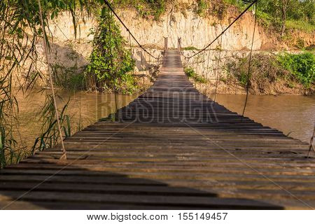 Old wooden sling brige hanging suspended above river in northern Thailand