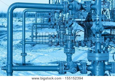 Group of wellheads. Oilfield during winter time. Oil and gas concept. Toned.