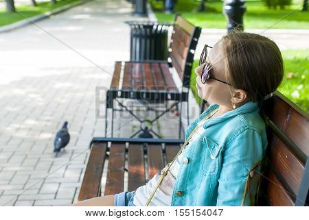 Portrait Of A Girl With Glasses On The Background Of  Tree Park