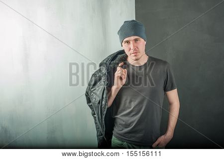 Studio Photography Young Brutal Guy. Man In T-shirt, Jeans And A Knitted Cap, Keeps Black Leather Ja