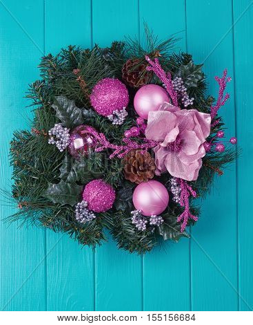 Christmas wreath on a rustic blue wooden front door.