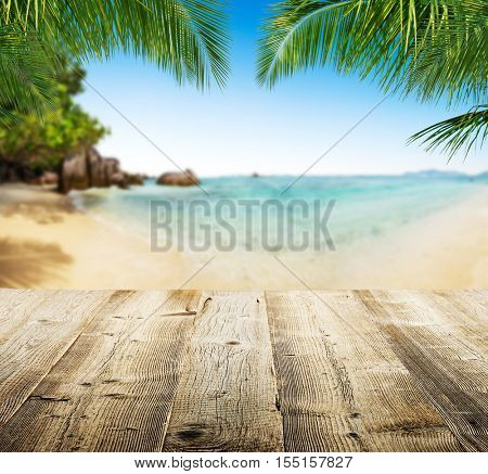 Empty wooden planks with tropical beach on background. Ideal for product placement