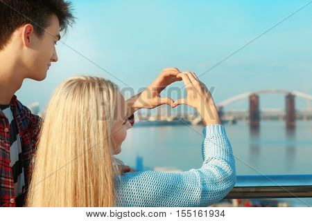 Portrait of beautiful young couple standing near handrail in park