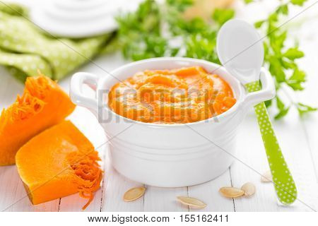 baby food, homemade pumpkin puree on white background