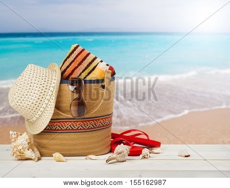 Bag sunglasses hat and flip flops on sea beach background