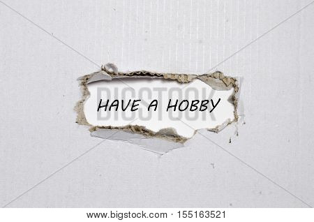 The word have a hobby appearing behind torn paper