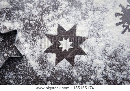 Cookie cutter and snowflake made of flour on grey table, close up view