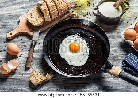Breakfast made of eggs and bread on old wooden table