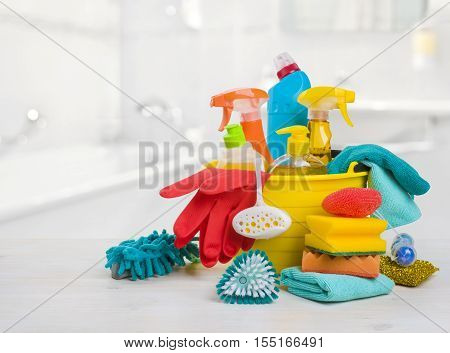 Bucket with chemical products on table over blurred bathroom background