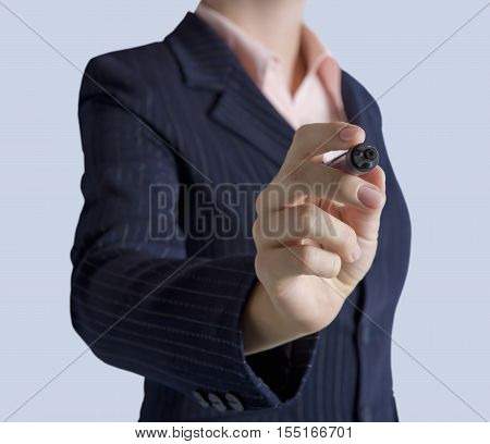 Business woman standing with marker in hand to draw on screen