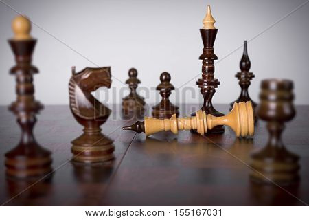 Chess pieces on chessboard. Checkmate to white king